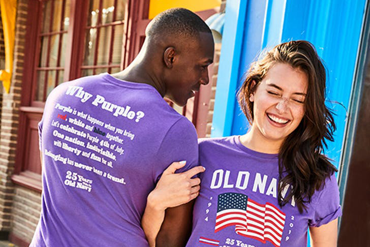 Two models wearing purple flag tees in honor of Old Navy's 25th Anniversary
