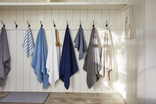 Bathroom towels in different patterns and shades hanging on wall hooks.