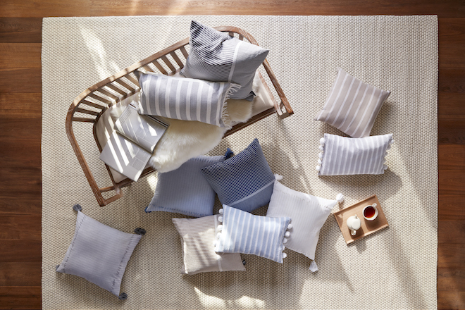 A pile of throw pillows in shades of blue, beige, and grey scattered on a beige rug.