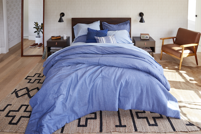 A bed is draped in different shades of blue bedding.