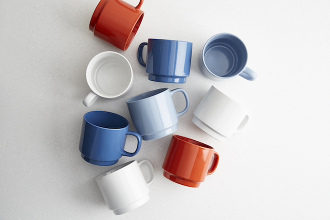 Nine mugs lay on their sides decoratively upon a tabletop.
